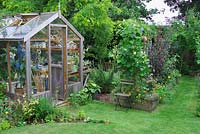 Garden view with wooden greenhouse and vegetable beds