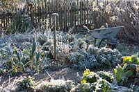 Frozen vegetable and herb garden with fork and wheelbarrow