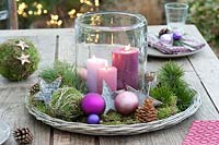 Christmas display on wooden table with Cyclamen, baubles and pine cones