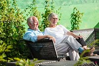 John and Sue Wright on seat at end of the Picket Beds. Hill House, Glascoed, Monmouthshire, Wales.