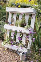 White pallet planter with garden tools and a mix of flowers, grasses and herbs