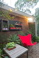 A seating area at night at the back of brick house with a bespoke recycled timber table and a retro style red canvas butterfly chair. A collection of mauve and red ceramic pots mounted on a black timber panel planted out with cactus and succulents.