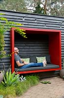 Garden owner and designer Steven Wells, relaxing in a red painted timber sitting pod he built, attached to a black painted timber wall.