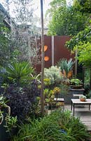 A sunken outdoor entertaining area with table and chairs, a heavily planted raised garden bed and decorative corten steel screens.