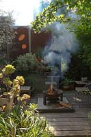 A sunken fire pit area with a freestanding metal fire pit, on a timber deck surrounded by raised garden beds and rusty coreten steel screens.