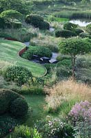 Overview of garden with countryside views beyond. Curving rusted Corten steel walls, Pinus mugo, clipped Crataegus x lavalleei 'Carrierei', Taxus baccata - Yew topiary, meadows and  natural pond. Borders with Stipa gigantea, Cenolophium denudatum, Eryngium giganteum, Thalictrum Elin and Rosa 'Rosemoor'.