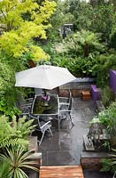 Small modern urban garden full of exotics with decking walkway over slate paving. Robinia pseudoacacia 'Frisia', metal table and chairs with a border of Ferns, Matteuccia struthiopteris, Equisetum japonicumon - Horsetail -  in raised pond.