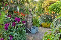 Patio amongst late summer borders in kitchen garden includes Tagetes tenuifolia 'Gnom', Dahlia 'David Howard', Santolina chamaecyparissus, Dahlia 'Thomas Edison' and Dahlia 'Garden Miracle'. Design: Alie Stoffers
