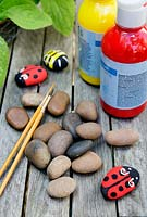 Garden craft making painted Bumble bees and Ladybirds with stones.  Materials needed - coloured paint, paintbrushes and stones