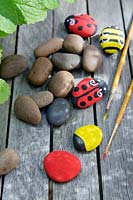 Garden craft making painted Bumble bees and Ladybirds with stones.  Paint the stones the solid base colour - red for the Ladybirds or yellow for the Bumble bees