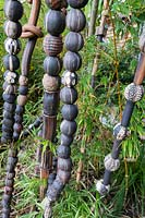 Vertical poles of pods and beads shoot through bamboo in sculptor and ceramicist Marcia Donahue's garden in Berkeley, California.