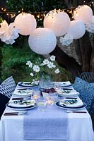 Outdoor dining table dressed in shades of blue and with a vase of white Japanese anemones.  Paper ball lanterns, fairy lights and paper pompoms hang over the table to decorate. Pockets are made in the folded napkins to put name card and each setting is finished with an olive branch.  Tealights are put on the table to light it up as dusk falls