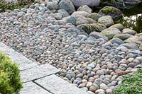 Details of the materials used in an Asian garden: densely stacked pebbles as transition from the boulders at the water edge to the flagstone paved garden path.