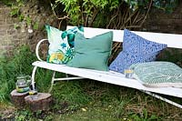 Bench in shady corner of the garden with cushions and a glass of water with lemon