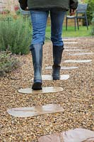 Woman in wellington boots walking on stepping stones through gravel garden