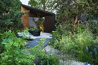 Pebble stone path leading to patio with block wood chairs surrounded by Pinus banksiana - Jack pine, Zizia aurea - Golden alexanders, Camassia quamash, Deschampsia cespitosa - The Royal Bank of Canada Garden - RHS Chelsea Flower Show 2017 - Designer: Charlotte Harris - Sponsor: RBC