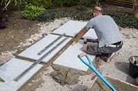 Making a mixed material patio - man using spirit level to ensure that large porcelain slabs are level