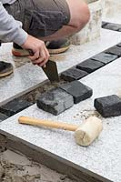 Making a mixed material patio  - man infilling space between large porcelain slabs with dark granite setts