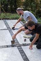 Making a mixed material patio - Men using jointing compound on patio with mix of large porcelain slabs and granite setts