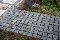 Making a mixed material patio - dark grey granite sett path, newly done not yet pointed