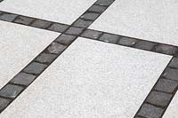 Making a mixed material patio - detail of paving where large porcelain slabs are mixed with granite setts