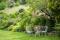 Vintage styled metal garden furniture at the end of a sloped garden with roses, box and perennials. Plants include Alchemilla mollis, Buxus, Hemerocallis, Paeonia and Rosa