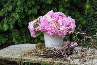 Bunch of pink Peonies in a white container on a stone table with a wreath and some hazel twigs