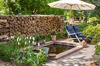Patio with deckchairs next to stone pond in front of a wood pile. Containers of Box and white tulips