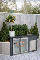 Outdoor kitchen with sink and freezer and small orange tree in a white planter plante r- The Retreat, RHS Malvern Spring Festival 2017 -