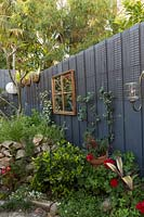 Painted timber fence with window framed mirror, climbing plants, and raised bed of found sandstone.