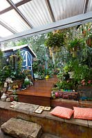 View from the covered entertaining area to a raised garden, timber deck, blue and white garden shed with an eclectic collection of pots and garden ornaments featuring a stone capped bench seat with orange patterned cushions and a large piece of sandstone as a step.