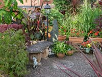 A gravel patio in front of a stone Bench with range of tropical planting including Canna's, Acer and Ricinus communis.
