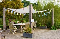 Wooden decking seating area with pergola fitted with shade sail and bunting