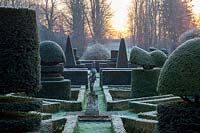 A formal garden with clipped topiary shapes in yew