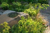 Roughly hewn sandstone boulder and foliage planting in The M and G Garden, RHS Chelsea Flower Show 2016. Designer Cleve West.