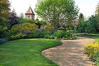 John Brookes garden, 'Denmans' near Chichester, West Sussex, England. Curving lawns, gravel paths, shrub borders and clock tower