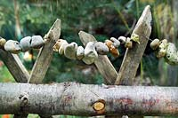 Rustic chestnut wooden fence with garden behind
