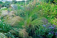 Isabelle van Groeningen's garden Large perennial bed with flowers ornamental grass Stipa Nigella damascena  Lavender Eryngium