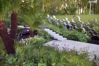 Chelsea Show Garden with water feature, tree fern foliage, perennial planting, wall of steel rings or circles by Andy Sturgeon