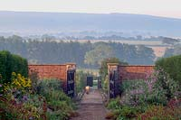 Barleywood Walled Garden, Wrington, Somerset, UK. Late summer in large organic vegetable garden with views across Somerset. Long paved paths between wide borders