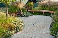 A curved gravel path and bench surrounded by soft planting including Lotus hirsutus, Sesleria autumnalis, Deschampsia cespitosa 'Goldtau', Astrantia 'Shaggy', Heuchera 'Palace Purple', Erigeron karvinskianus, Corylus colurna and Phormium tenax 'Platt's Black, The Between the Lines Garden, RHS Hampton Court Flower Show, 2013.