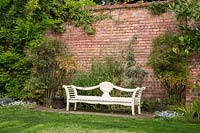 A white wooden garden bench stands in front of a brick stone wall at Newby Hall and Gardens, Yorkshire.