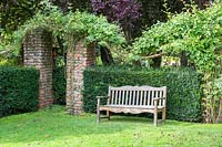Wooden garden bench backed by Taxus baccata - Yew - hedge at Newby Hall and Gardens, Yorkshire.