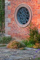 Spider's web style circular window with flower bed at Morton Hall Gardens, Worcestershire