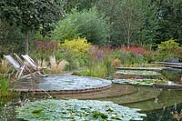 Two deckchairs set on patio by natural swimming pool at Ellicar Gardens, Nottinghamshire.