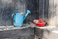 A child's watering-can and a toy boat are left on the edge of the sandpit.