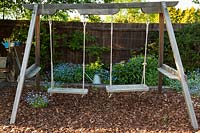 A view of a double wooden swing set.