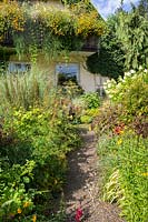 View of gravel path leading though summer flowering borders.