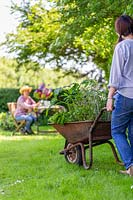 Woman pushes wheelbarrow planted with mixed herbs towards woman sitting at table on a lawn.