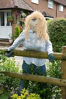 Female scarecrow with blond hair and a glass of wine leaning on wooden fence, Bayford, Hertfordshire, UK.